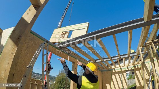 Construction worker pointing while crane loading construction frame at construction site.