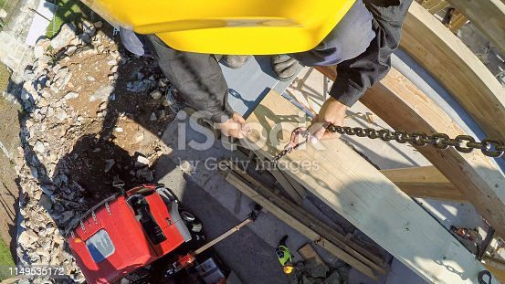 Construction worker attaching chain to wooden plank at construction site.
