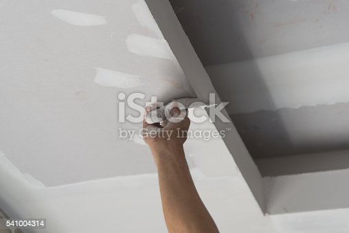 istock Worker working manual with wall plastering tools inside a house 541004314