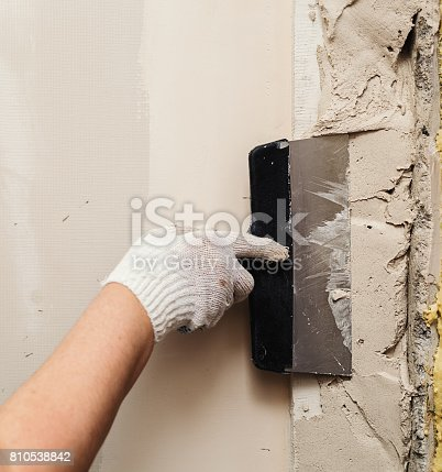 istock Worker working manual with wall plastering tools inside a house 810538842