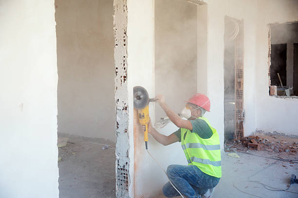Worker working on the wall with saw stock photo