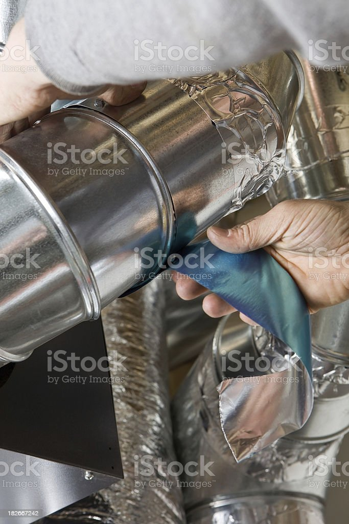 Worker Wrapping an HVAC Air Duct with Foil Tape royalty-free stock photo