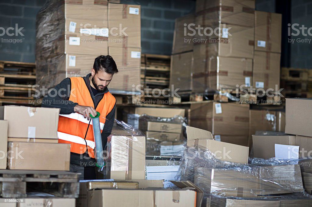 Worker wrapping cardboard boxes in the warehouse stock photo