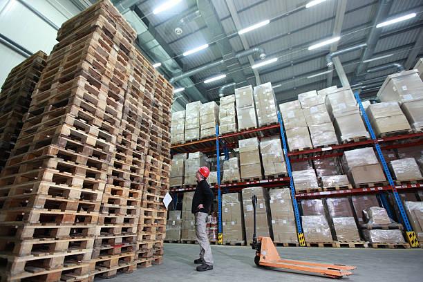 arbeiter, palettenhubwagen, stapel holz paletten im storehouse - papierrollenhalter stock-fotos und bilder