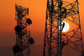 istock Workers are climbing to repair the telecommunication tower or poles,Red sky sunset background 978340120