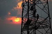 istock Workers are climbing to repair the telecommunication tower,Red sky sunset background 978336120