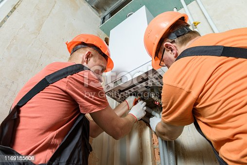Workers are connecting the heating system pipes to the gas boiler.