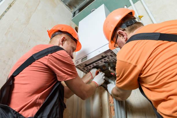 Arbeiter verbinden die Rohre mit dem Gaskessel. – Foto