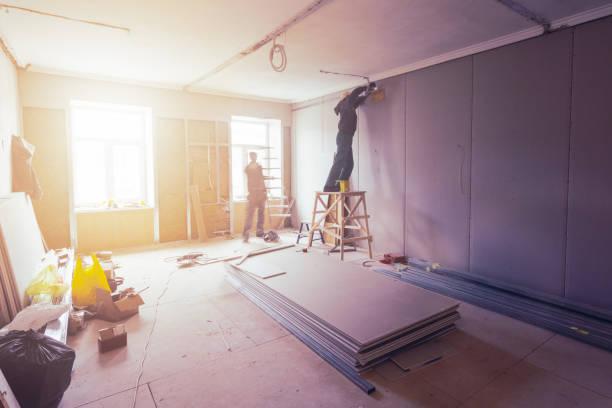 Trabalhadores são instalação de gesso acartonado (drywall) para paredes de gesso no apartamento está em construção, remodelação, renovação, extensão, restauração e reconstrução. - foto de acervo