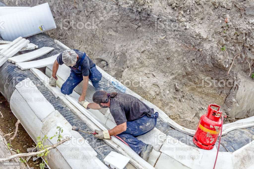 Workers are placing set of Styrofoam thermal insulation on new pipeline in trench stock photo