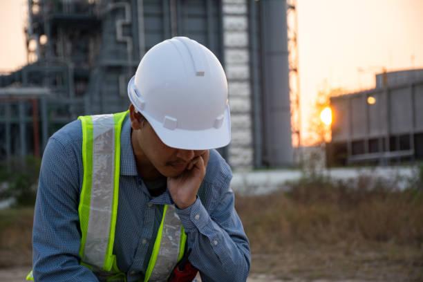 Trabajadores asiáticos hombre sentado estresado. en la central eléctrica. Área de energía energética. concepto de trastorno depresivo mayor, desempleado, tristeza, depresión y problemas humanos - foto de stock