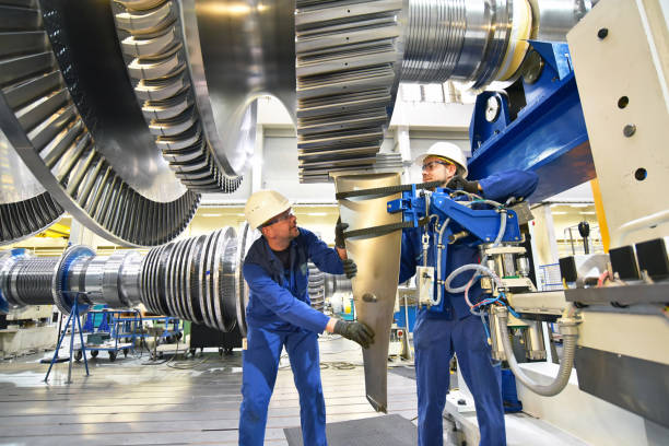 workers assembling and constructing gas turbines in a modern industrial factory workers assembling and constructing gas turbines in a modern industrial factory turbine stock pictures, royalty-free photos & images