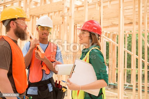 488715470istockphoto Workers at construction job site inside framed building. 596800366