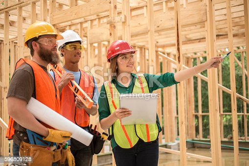 istock Workers at construction job site inside framed building. 596809128