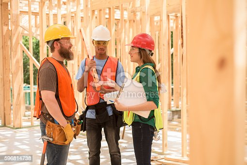 488715470istockphoto Workers at construction job site inside framed building. 596814738