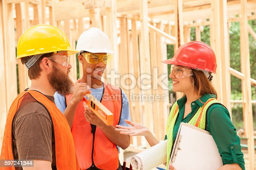 488715470istockphoto Workers at construction job site inside framed building. 597241344