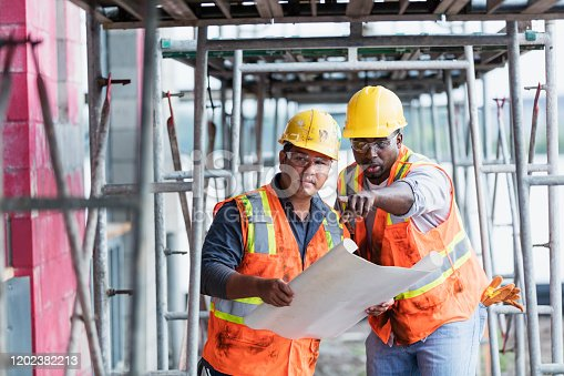 Two multi-ethnic men working at a construction side wearing hard hats, safety glasses and reflective vests, looking at plans. They are inside the structure being built. The taller one is a mid adult African-American man in his 30s. The other one, holding the plans, is a young Hispanic man in his 20s.