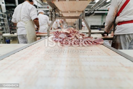 istock Workers at meet industry handle meat organizing packing shipping loading at meat factory. 1049948424