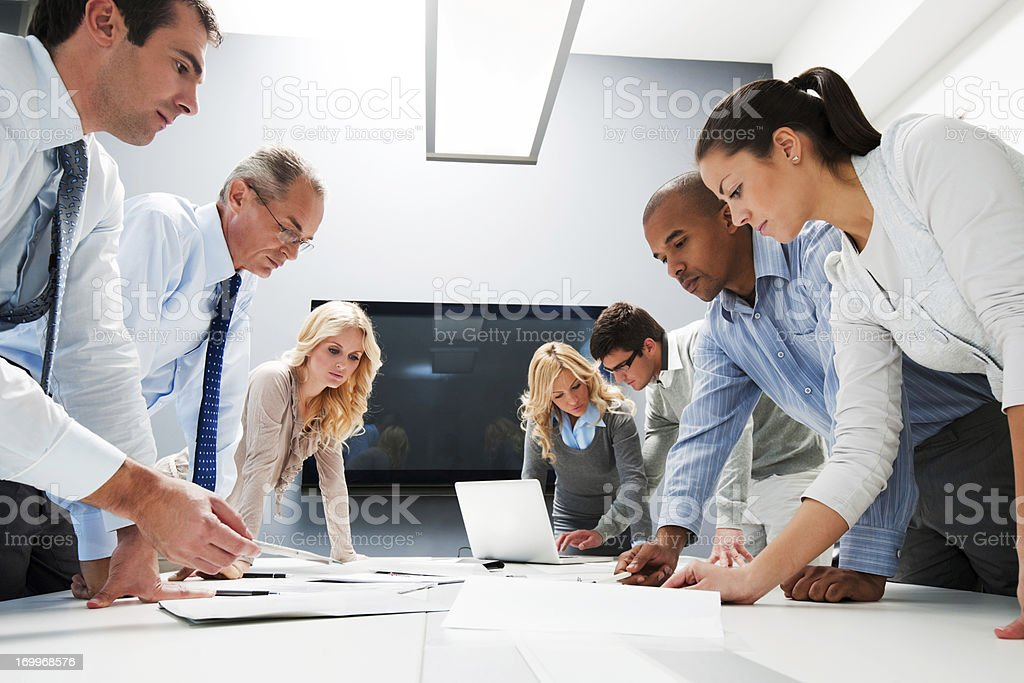 Workers at office meeting standing to see reports royalty-free stock photo