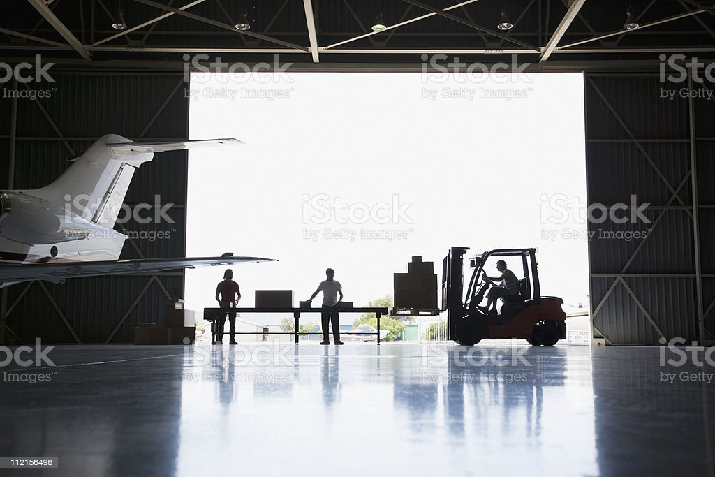 Workers, boxes and forklift in hangar stock photo