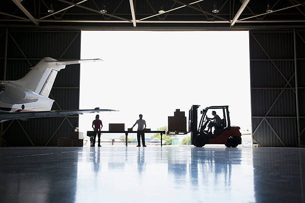 Workers, boxes and forklift in hangar  airplane hangar stock pictures, royalty-free photos & images