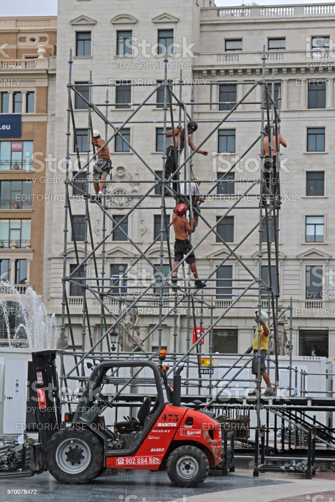 Workers build a metal structure for the stage in the town square in...