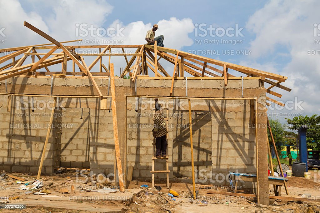 Workers building a wooden house in Nigeria, Africa stock photo