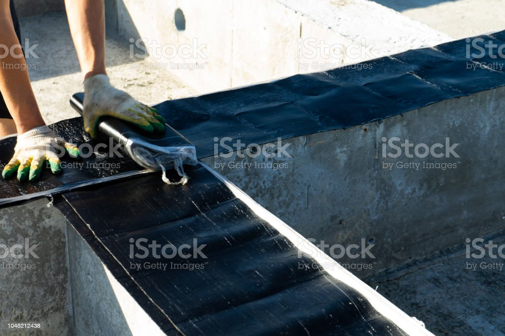 Workers carry out waterproofing of the Foundation for the construction of a wooden house. stock photo