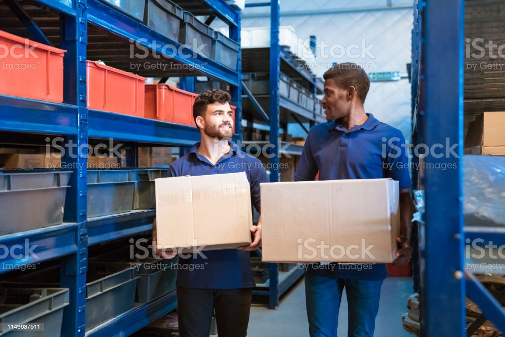 Workers carrying cardboard boxes in factory Workers carrying cardboard boxes by racks. Colleagues are standing in distribution warehouse. They are wearing uniform. 20-24 Years Stock Photo