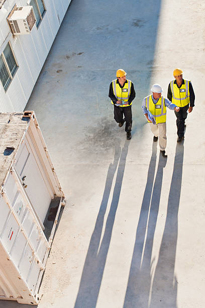 Workers casting shadows on site stock photo