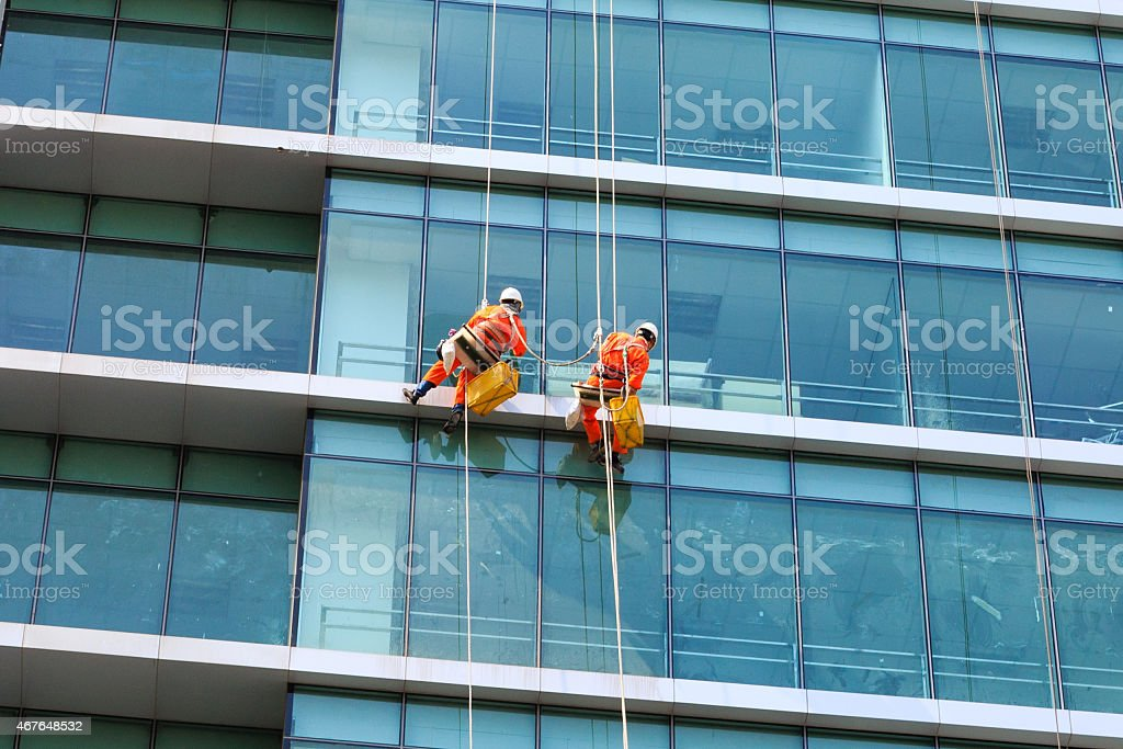 Workers clean the glass on tall buildings - Royalty-free 2015 Stockfoto