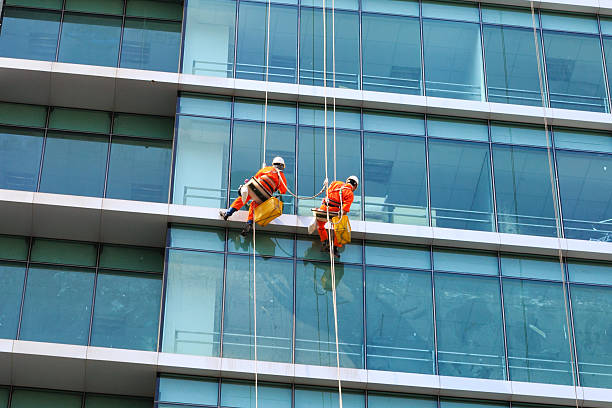 Workers clean the glass on tall buildings stock photo