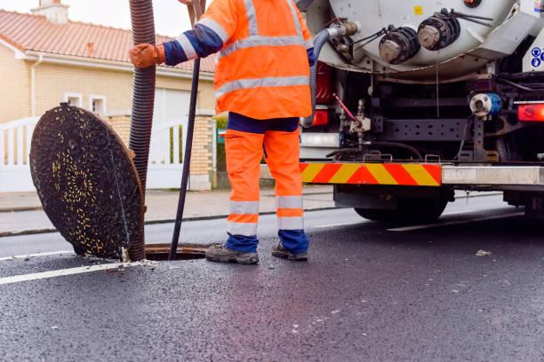 arbeiter, die die kanalisation auf den straßen reinigen und warten - kanalisationsabflüsse stock-fotos und bilder