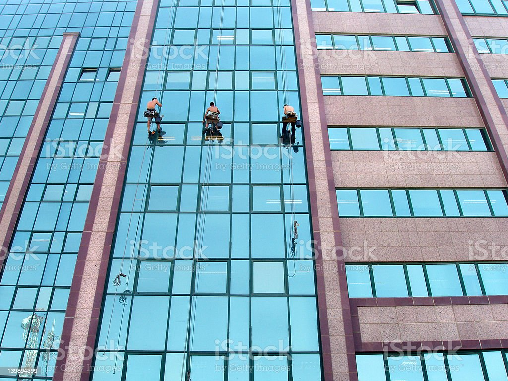 Workers  cleaning the windows of a corporate building. stock photo