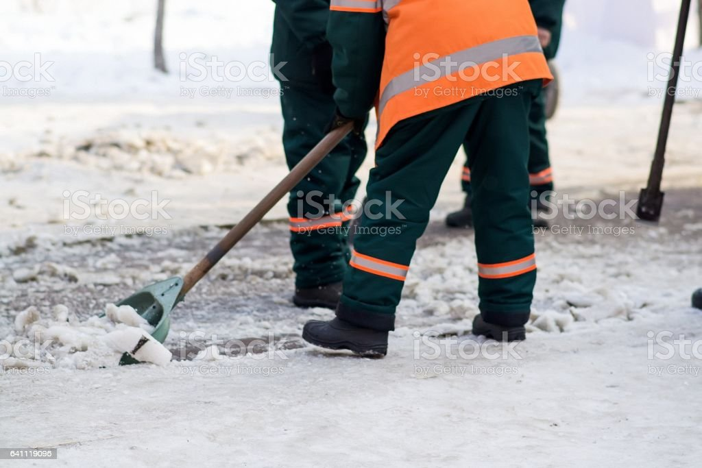 Workers cleans snow shovel stock photo
