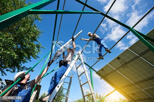 istock Workers command installing solar panels on the roof. 1008852154