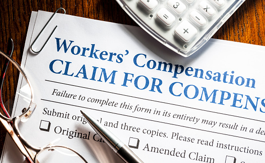 Workers' Compensation form with pen and glasses