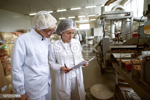 Two female workers controling food quality in food factory. One of them holding papers and pen and other looking at papers.