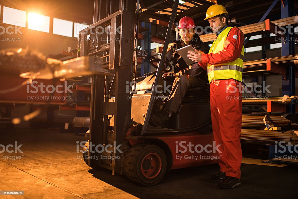 Workers cooperating while using digital tablet in a warehouse. – Foto