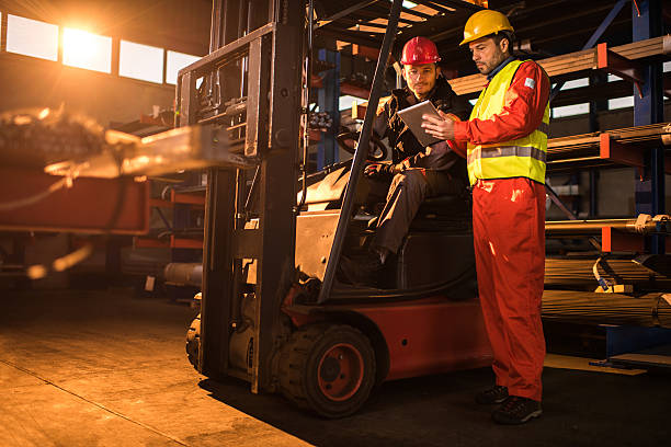 Workers cooperating while using digital tablet in a warehouse. stock photo