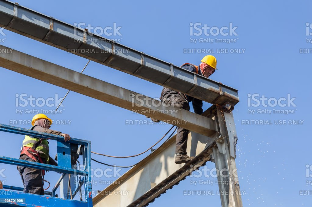 Workers cutting metal structure high above stock photo
