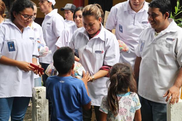 trabajadores entregan dulces a los niños - ayuda humanitaria fotografías e imágenes de stock
