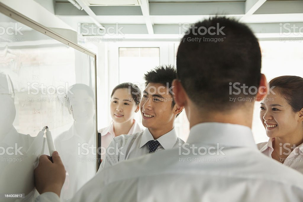Workers discussing a diagram on the whiteboard stock photo