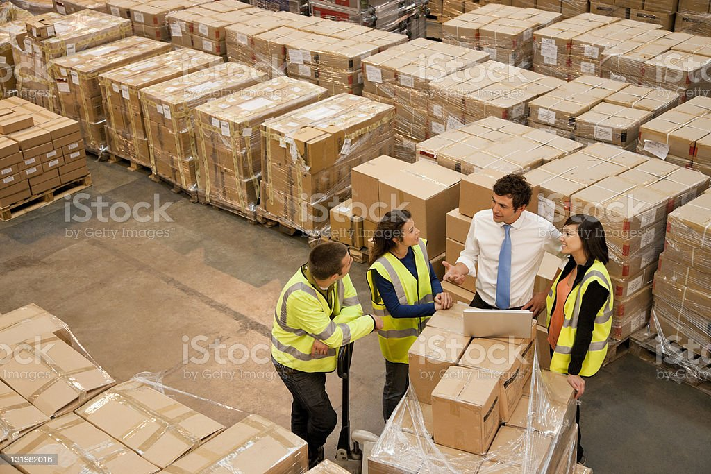 Workers discussing a project in warehouse royalty-free stock photo