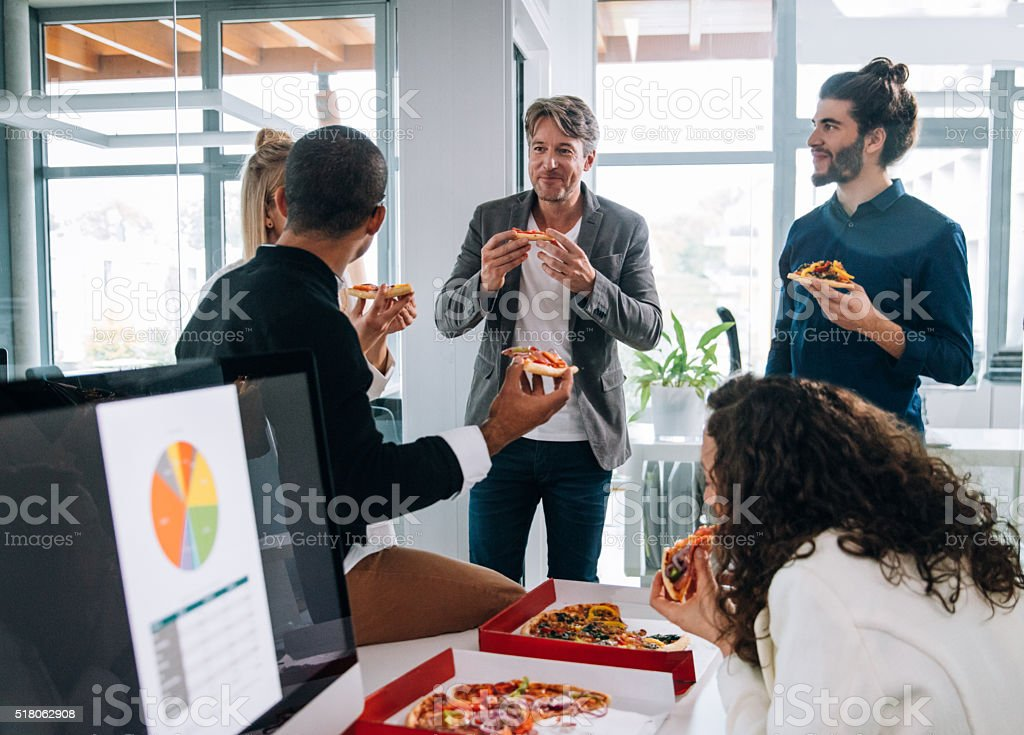 Workers  discussing concepts whilst eating pizza for a group meeting stock photo