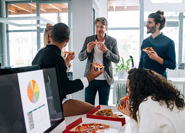 workers  discussing concepts whilst eating pizza for a group meeting - eating technology stock photos and pictures