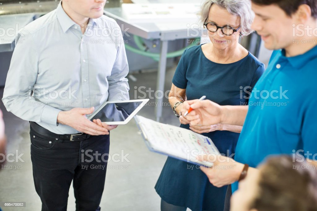 Workers discussing with manager at printing plant stock photo