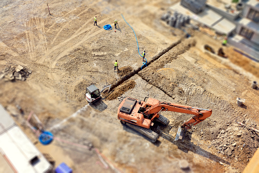 Manual workers and Engineers are digging a raw in the ground, they do drainage, sewer system, then make a new asphalt road. Directly above, tilt-shift.