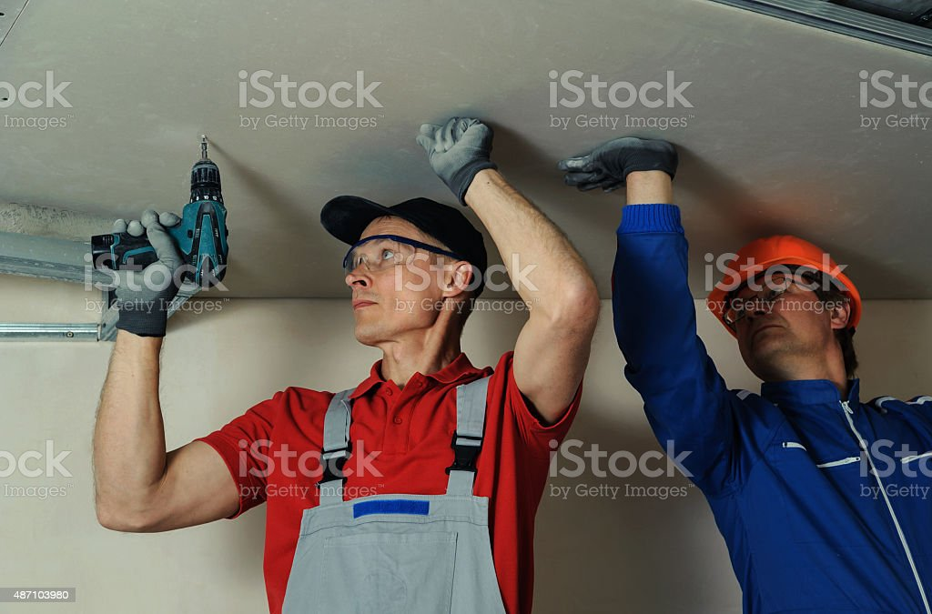 Workers fixes the drywall stock photo