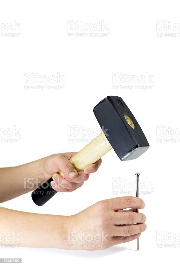 Worker's Hands Gripping Hammer While Driving A Nail Isolated stock photo